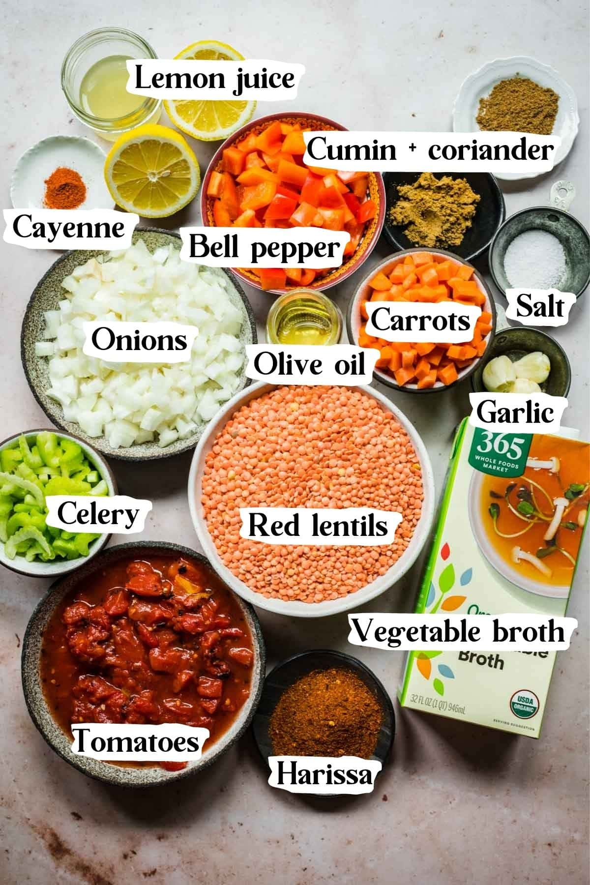 Overhead view of red lentil soup ingredients, including spices and vegetable broth.