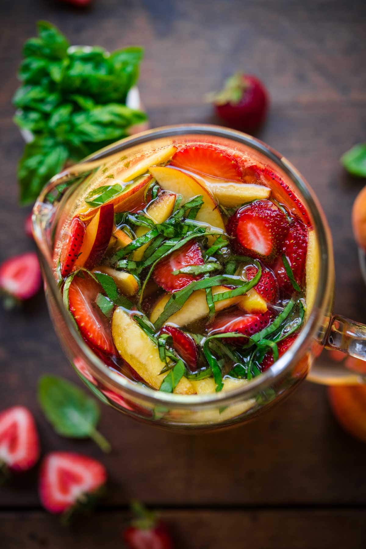 Overhead view of a pitcher of sangria with cut up strawberries, peaches, and basil.