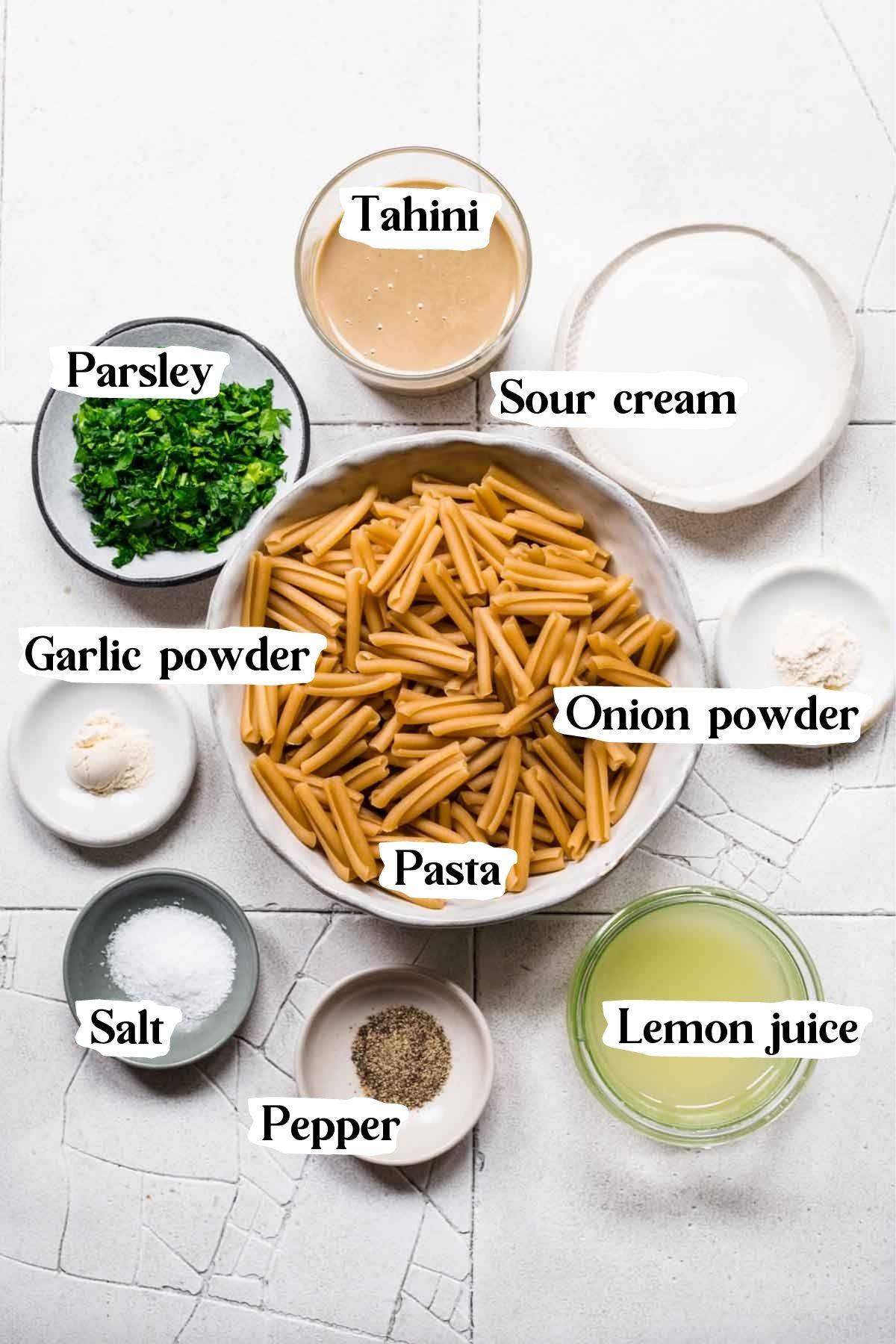 Overhead view of ingredients used in the tahini pasta, including tahini, parsley, and lemon juice.