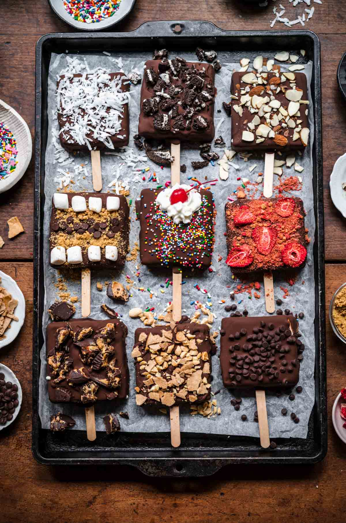 overhead view of vegan ice cream bars with various toppings on a sheet pan.