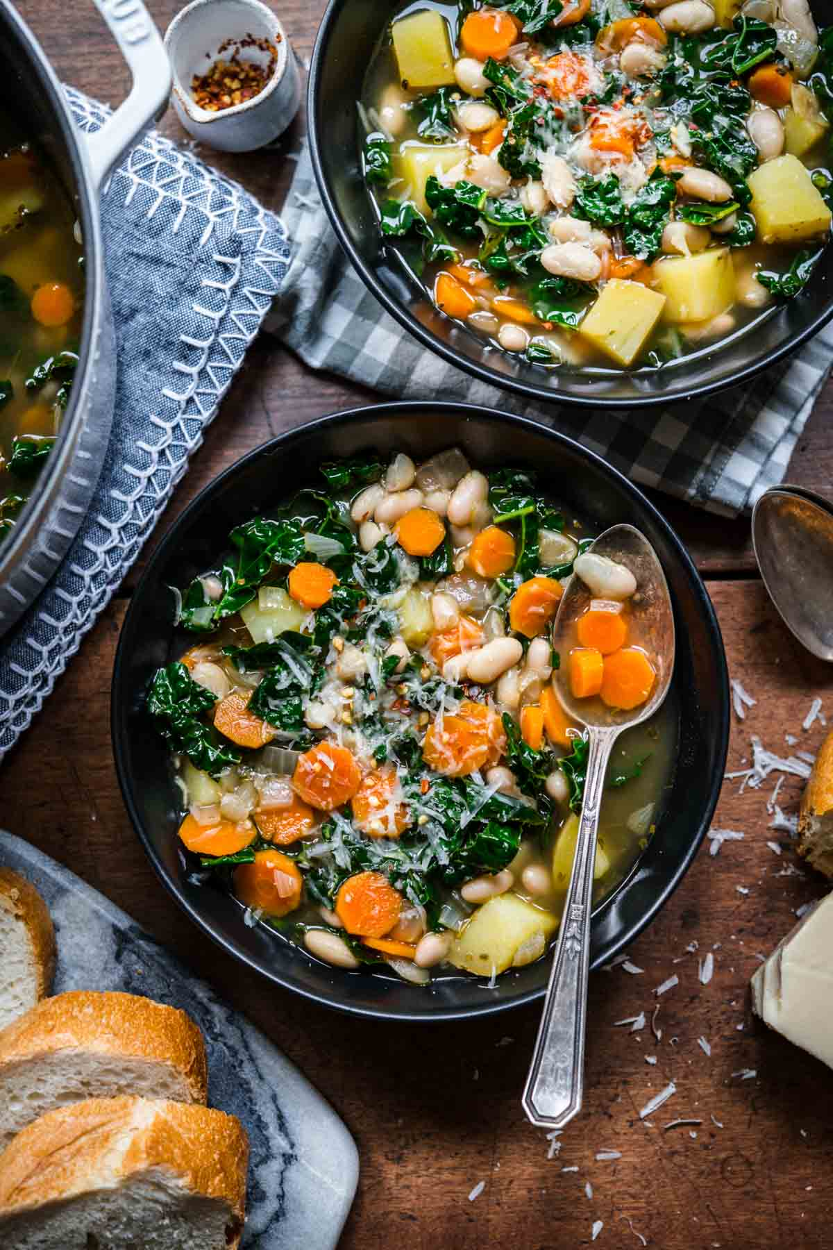 Overhead view of two bowls of white bean and kale soup with beans, carrots, and kale.