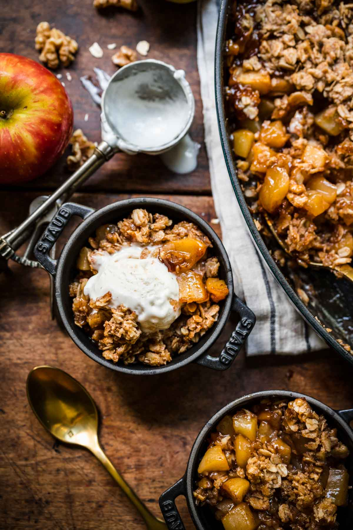 overhead view of vegan apple crisp served in mini cocottes with vanilla ice cream on top on wood table.
