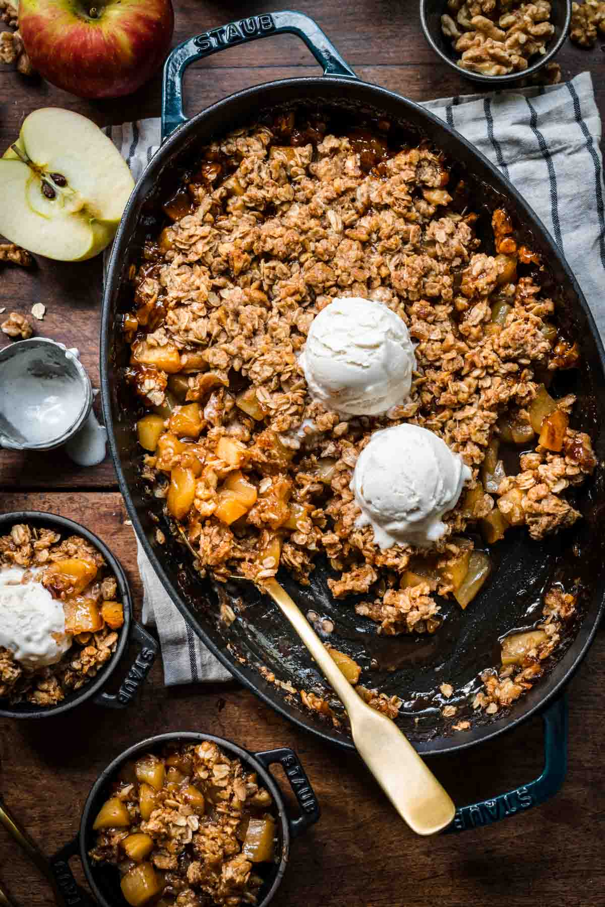 overhead view of gluten free apple crisp in an oval cast iron skillet with vanilla ice cream on top and serving spoon.