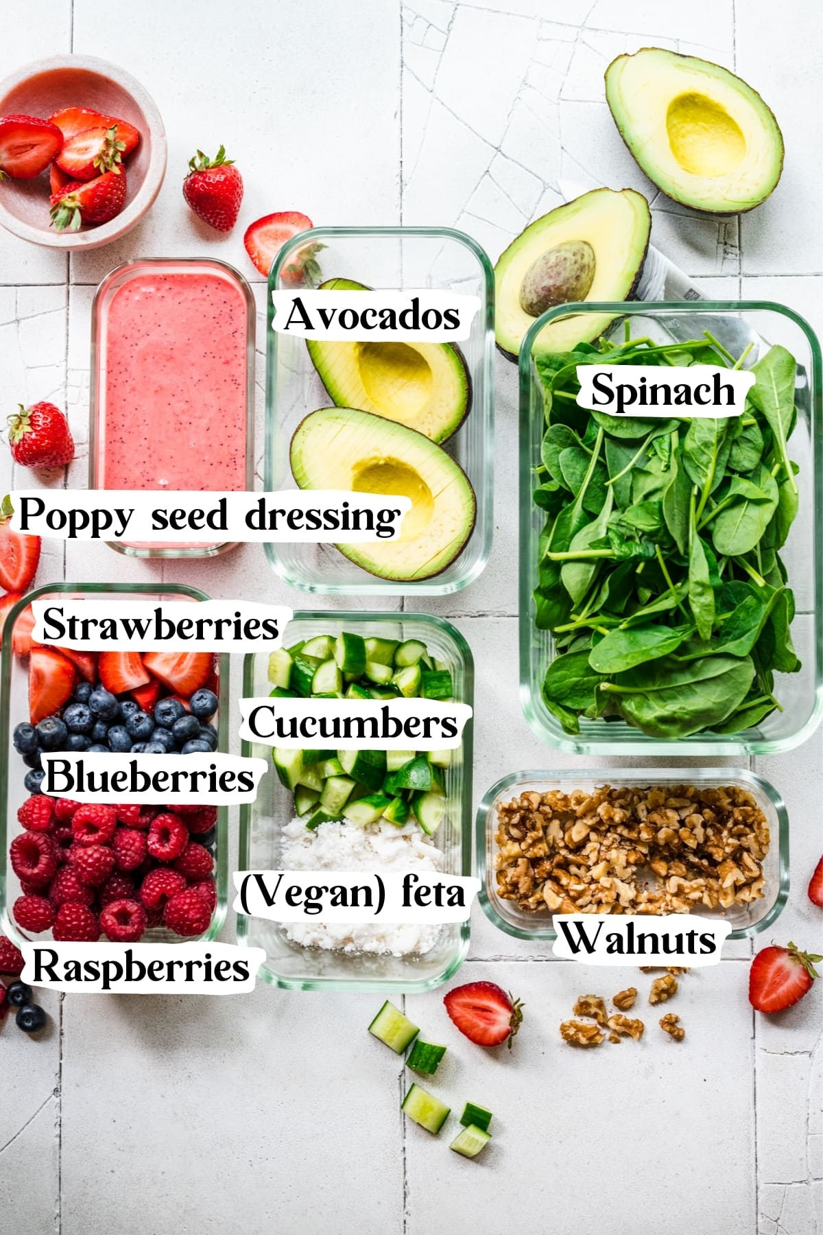overhead view of ingredients for berry avocado salad in separate tupperware containers.