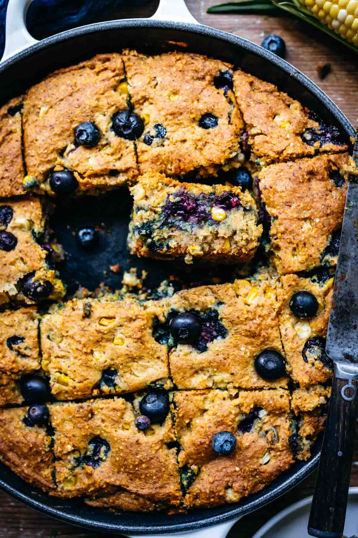 Close up overhead view of blueberry cornbread in a skillet.