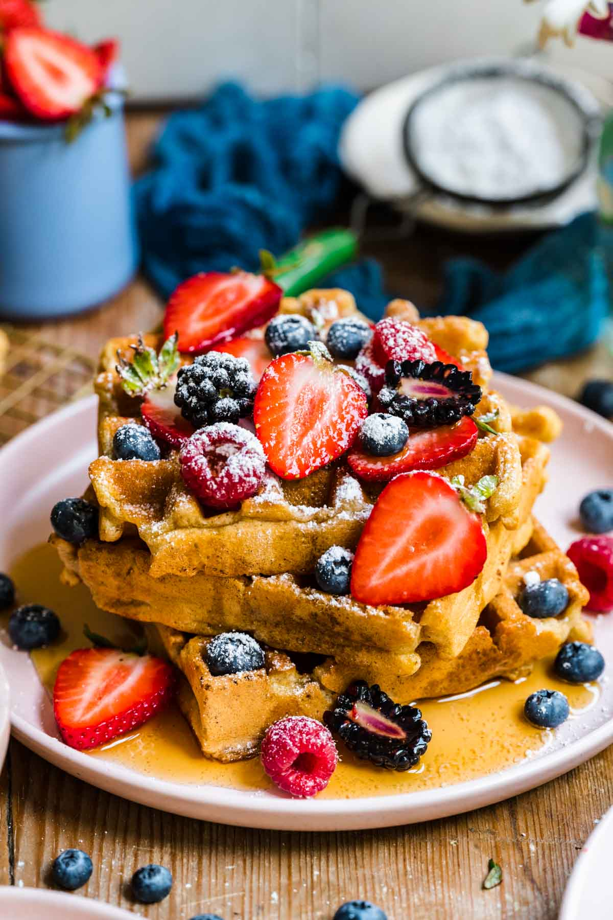 side view of a stack of vegan and gluten free waffles topped with berries, maple syrup and powdered sugar.