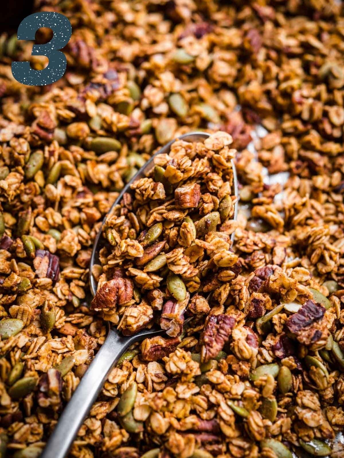 Granola on a sheet pan with some of it in a spoon facing the camera.