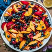 overhead view of summer fruit salad with stone fruit and berries on large white platter.