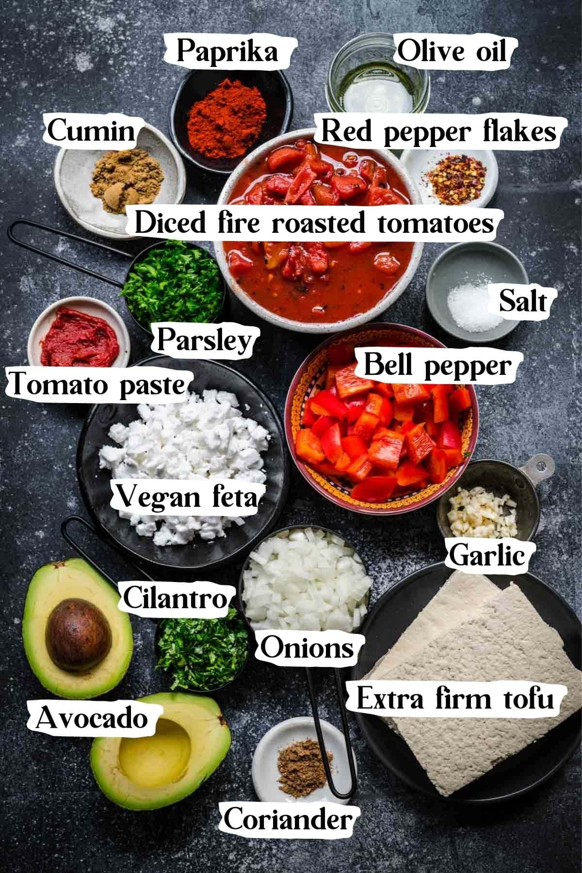 Overhead view of vegan shakshuka ingredients, including tofu, spices, avocado, and feta.