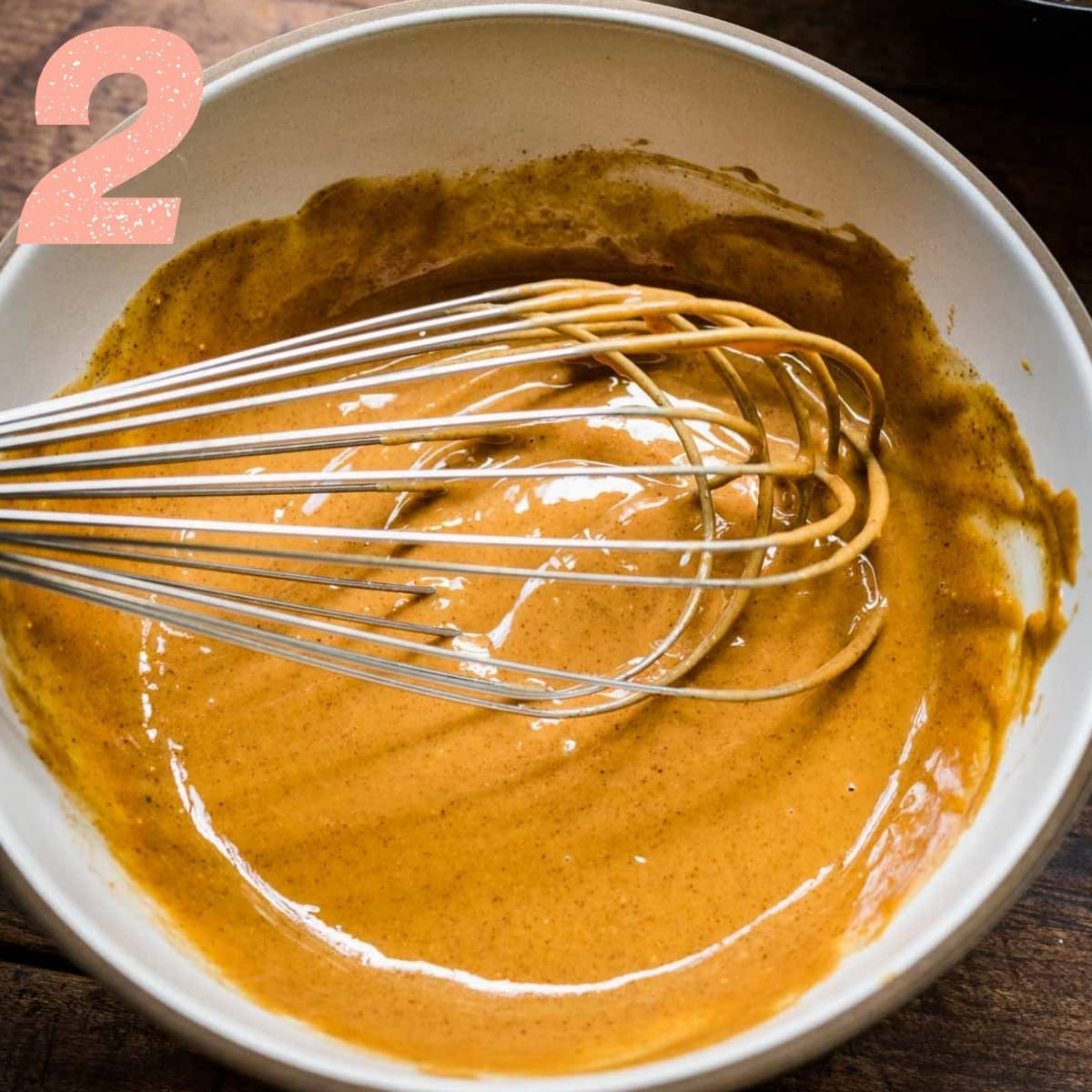 close up view of peanut butter filling in a mixing bowl with whisk.