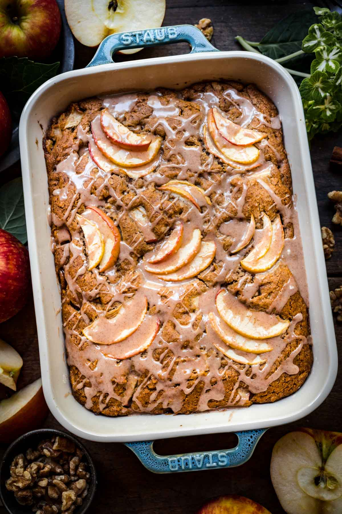 Overhead view of finished apple walnut cake with glaze in a baking dish.