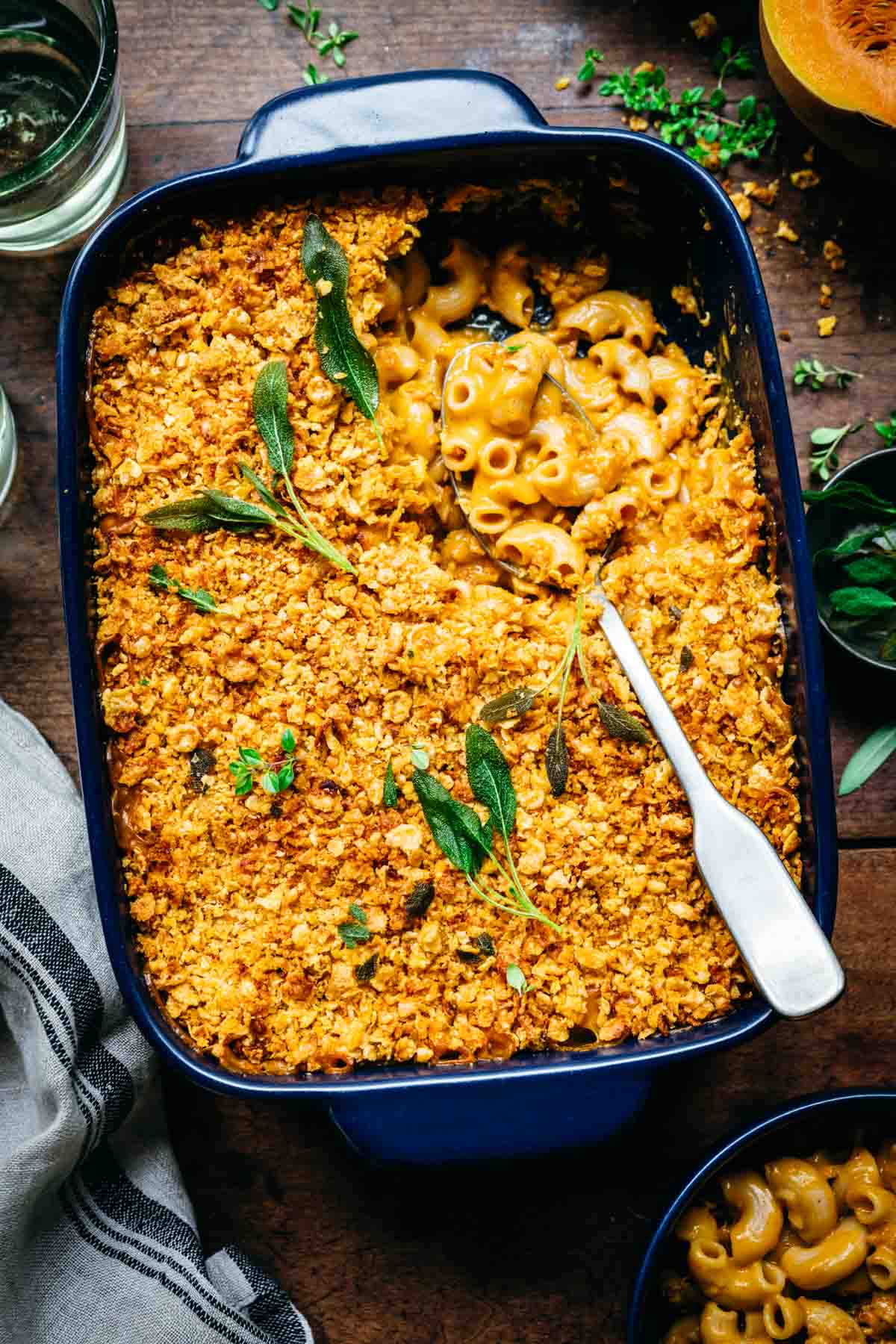 overhead view of vegan butternut squash mac and cheese with breadcrumbs in baking pan with crispy sage on top.