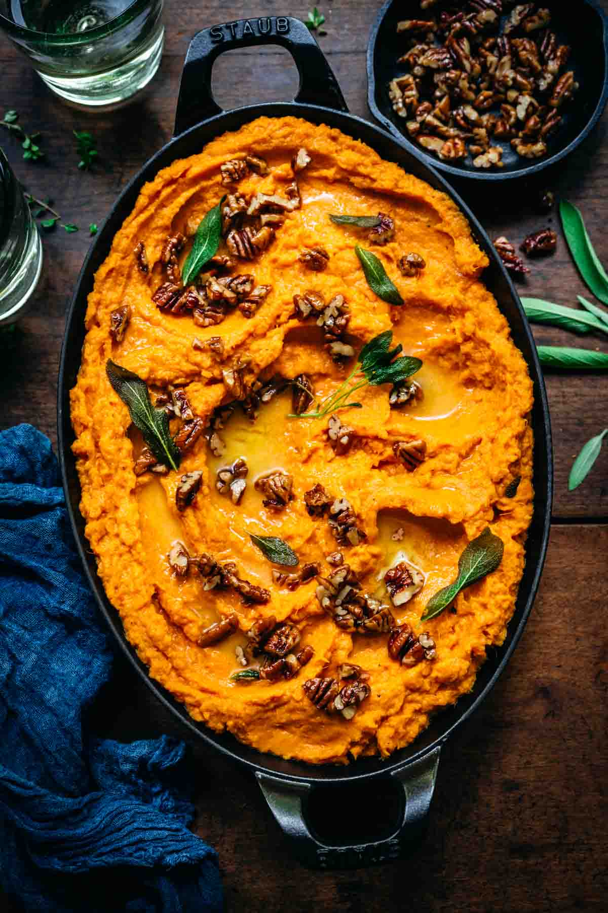 Overhead view of mashed sweet potatoes with pecans and herbs.