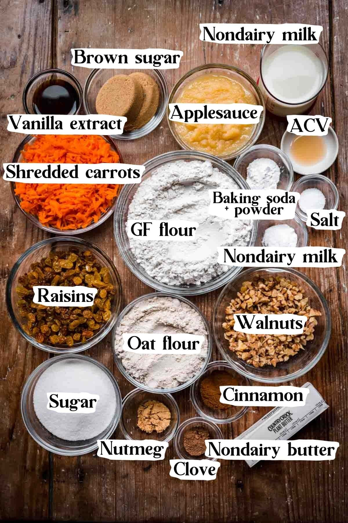 Overhead view of vegan carrot cake ingredients, including flour, sugar, carrots, and milk.