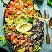 overhead view of fajita vegetable salad with black beans and avocado on a large platter.