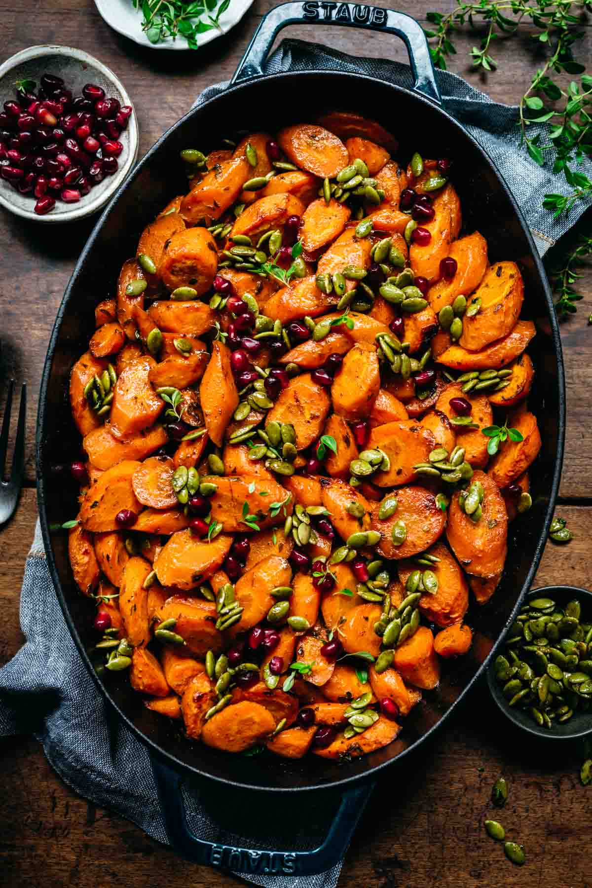 Overhead view of glazed carrots in a pan with pomegranate and pumpkin seeds.