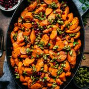 Close up view of maple glazed carrots in a pan garnished with pumpkin seeds and pomegranate.