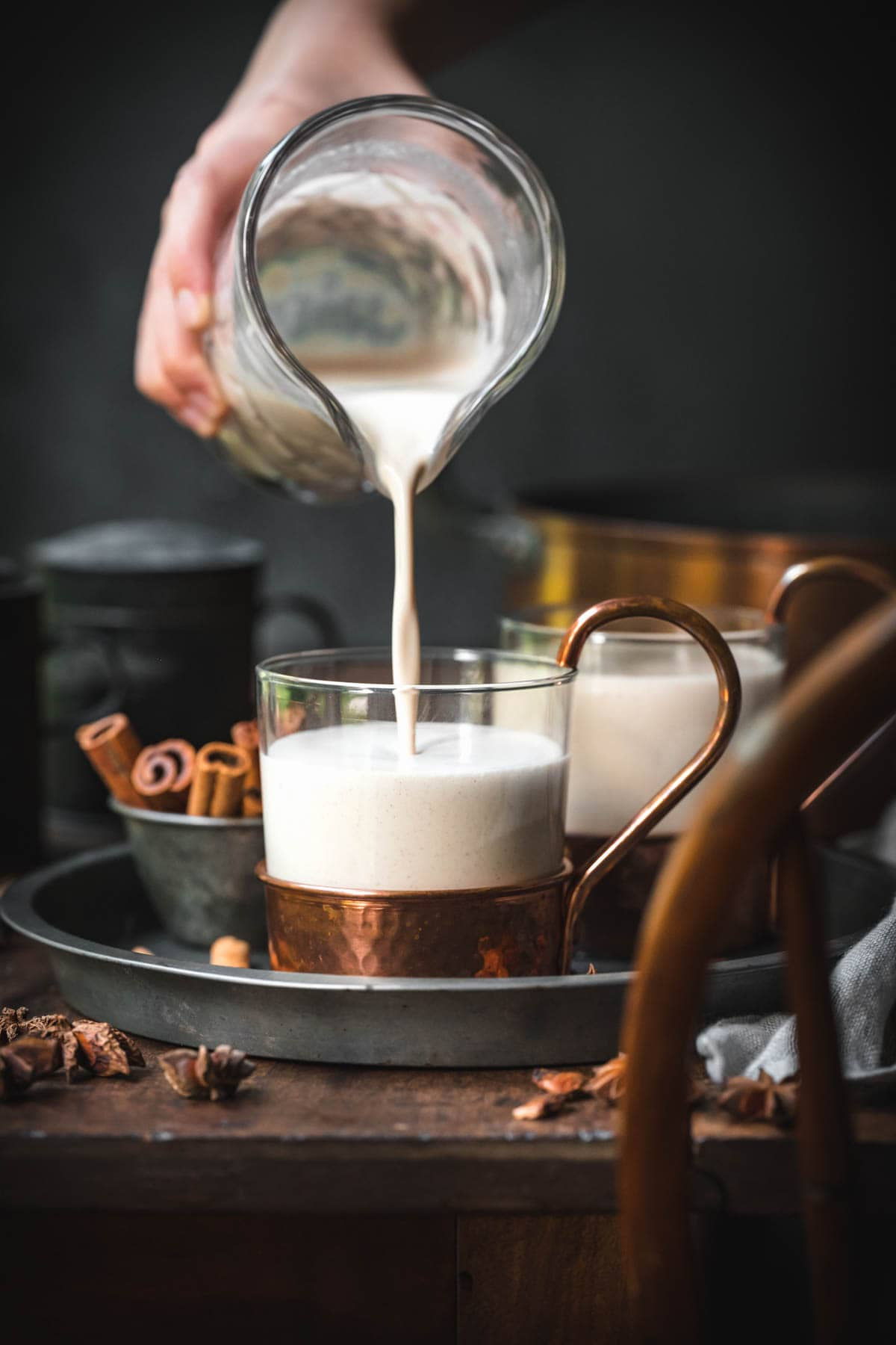 Vegan eggnog being poured into a glass.