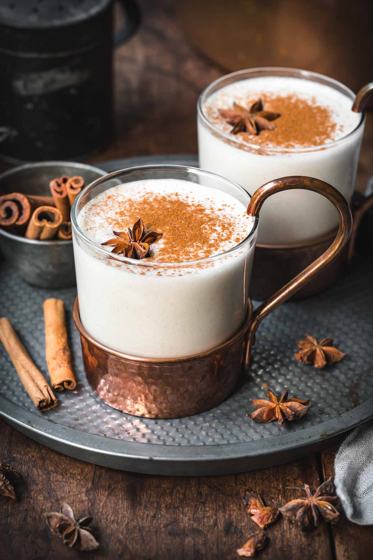 Close up of vegan eggnog in a mug with cinnamon on top and star anise.