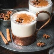 Close up shot of vegan eggnog in a transparent mug with cinnamon and anise.