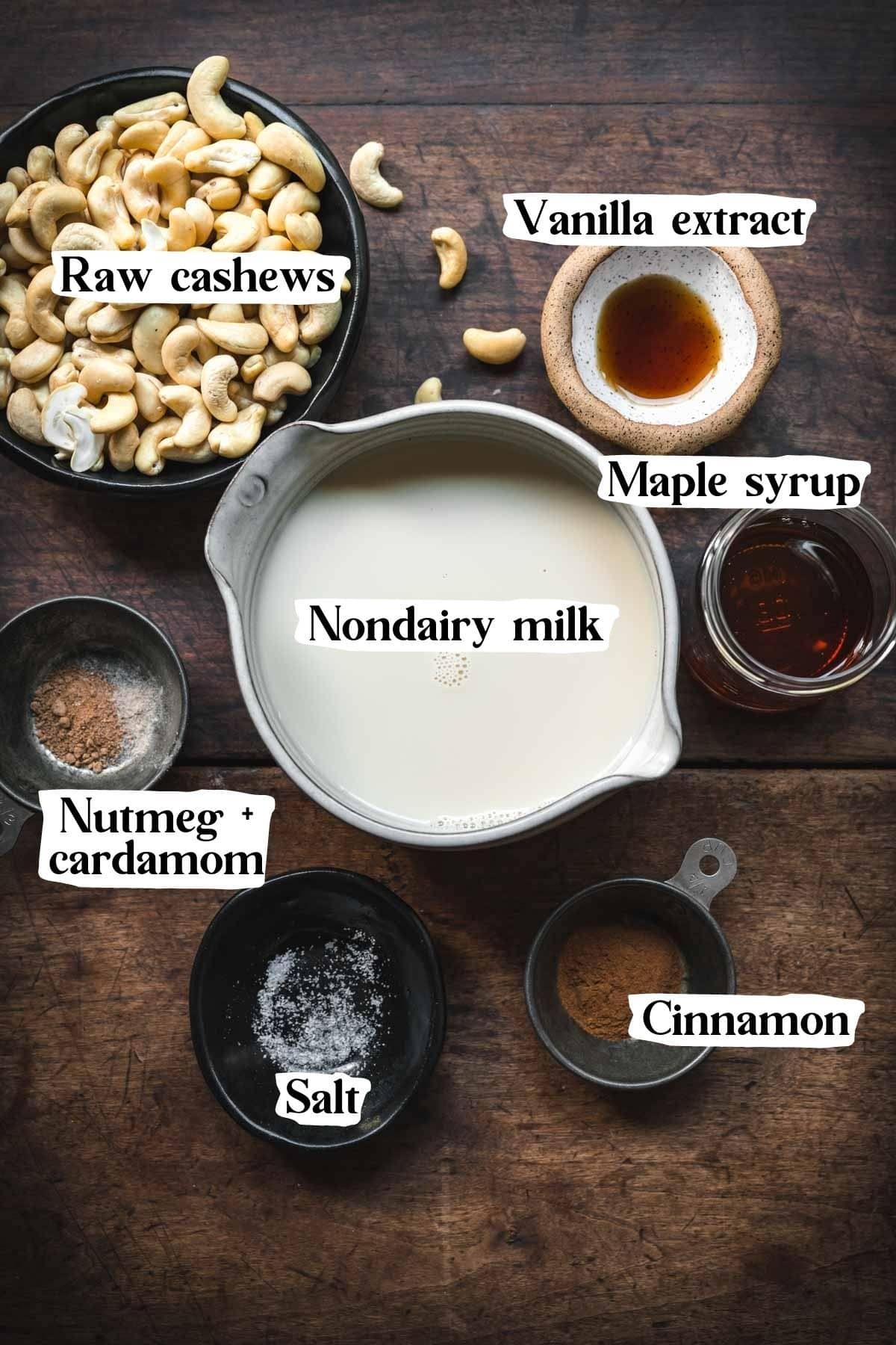 Overhead view of vegan eggnog ingredients, including cashews, vanilla extract, milk, maple, nutmeg, salt and cinnamon.